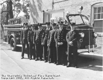Members of the Cherrydale VFD pose in front of an American LaFrance engine which ran from the Cherrydale station. The firefighter on the left is Sam Felzter and the firefighter second from the right is Marvin Binns, who still serves the CVFD as its president, over thirty years after this picture was taken.
