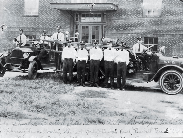 Photo of 8 uniformed firefighters with two pieces of fire apparatus.