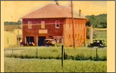 Cherrydale fire house pictured in the 1920's. Two story red brick fire station adjoining a white single story structure and otherwise surrounded by fields. Two cars are parked by the fire station.